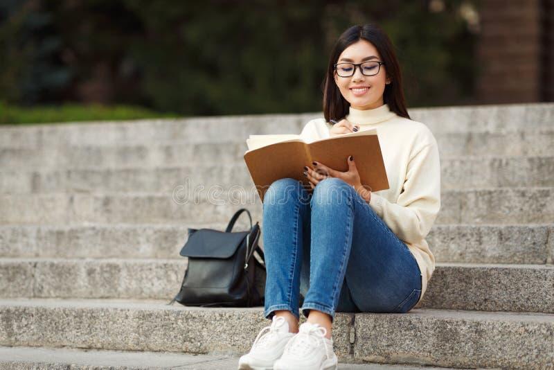 Ευτυχείς σημειώσεις γραψίματος σπουδαστών στο σημειωματάριο, που κάθεται στα σκαλοπάτια στοκ εικόνες με δικαίωμα ελεύθερης χρήσης