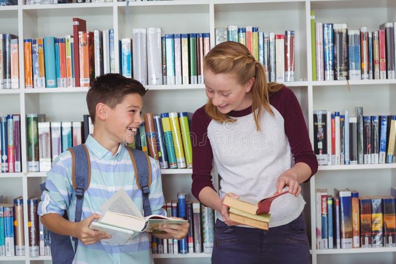 Ευτυχείς σπουδαστές που διαβάζουν τα βιβλία στη βιβλιοθήκη στοκ φωτογραφία