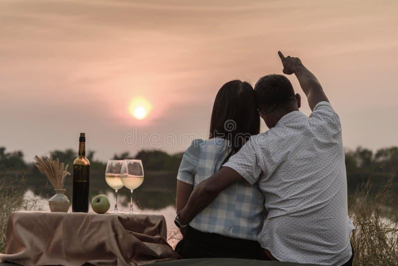 Ευτυχείς στιγμές ζωής Ζεύγος που απολαμβάνει το ηλιοβασίλεμα ενώ έχοντας ένα ποτήρι του κρασιού στοκ εικόνες