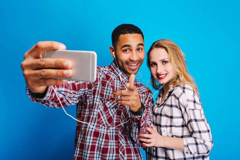 Ευτυχείς στιγμές μαζί του συγκινημένου καλού ζεύγους που έχει τη διασκέδαση στο μπλε υπόβαθρο Παραγωγή selfie του πορτρέτου, εύθυ στοκ εικόνες