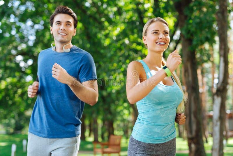 Ευτυχείς συμπαθητικοί ενεργοί άνθρωποι που απολαμβάνουν να τρέξει από κοινού στοκ εικόνες