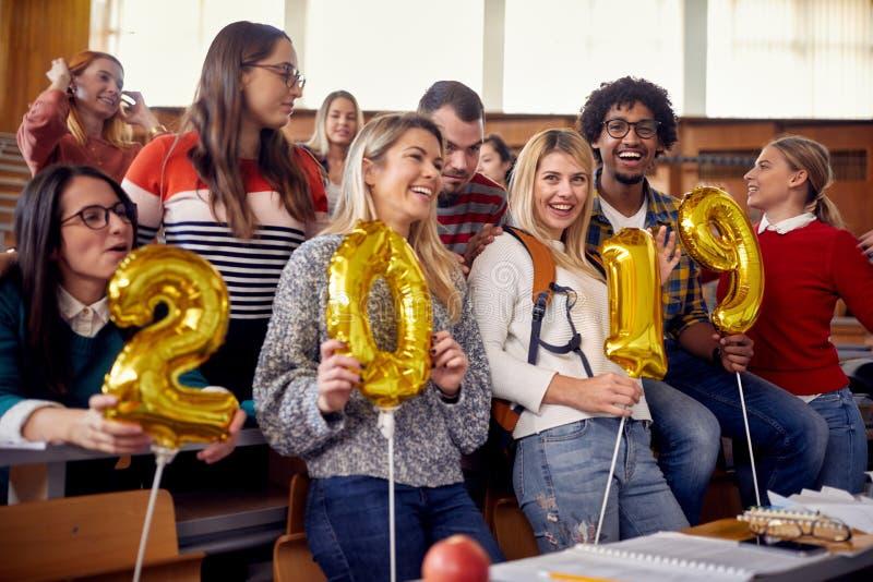 Ευτυχείς συνάδελφοι που έχουν τη διασκέδαση στο νέο εορτασμό έτους στο πανεπιστήμιο στοκ φωτογραφία με δικαίωμα ελεύθερης χρήσης