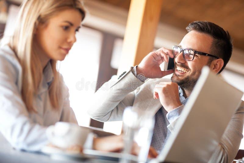 Ευτυχείς συνάδελφοι που εξετάζουν τη επιχειρηματία χρησιμοποιώντας το lap-top κατά τη διάρκεια της συνεδρίασης στοκ εικόνες