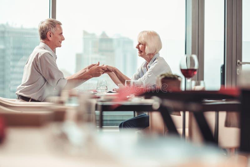 Ευτυχείς συνταξιούχοι που ξοδεύουν το χρόνο μαζί σε ένα εστιατόριο στοκ φωτογραφίες