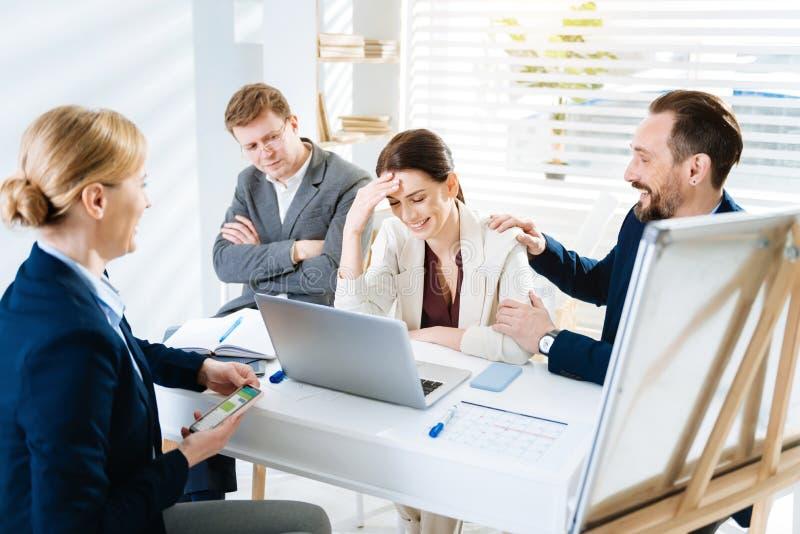 Ευτυχείς τέσσερις συνάδελφοι που γελούν μετά από την πίεση στοκ φωτογραφία με δικαίωμα ελεύθερης χρήσης
