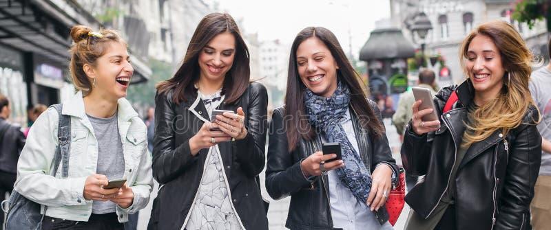 Ευτυχείς τέσσερις φίλοι που περπατούν στην οδό και που χρησιμοποιούν τα κινητά τηλέφωνα στοκ φωτογραφία με δικαίωμα ελεύθερης χρήσης