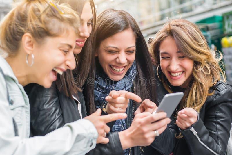 Ευτυχείς τέσσερις φίλοι που περπατούν στην οδό και που χρησιμοποιούν τα κινητά τηλέφωνα στοκ εικόνες