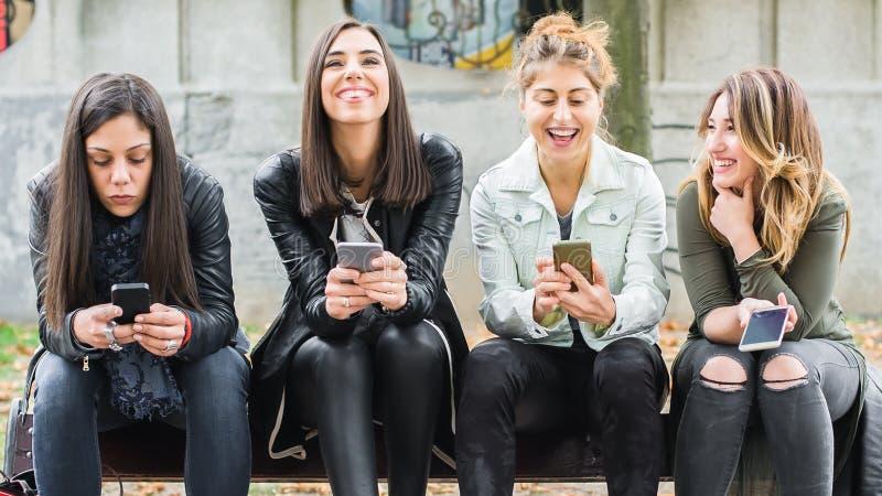 Ευτυχείς τέσσερις φίλοι που χρησιμοποιούν τα κινητά τηλέφωνα στον πάγκο πάρκων στοκ φωτογραφίες