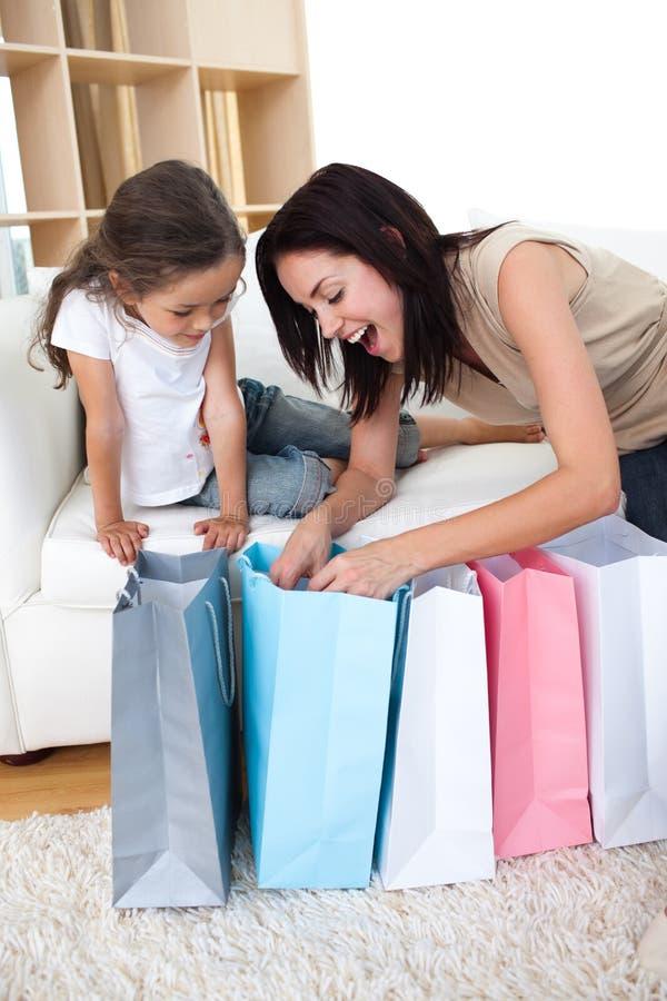 Ευτυχείς τσάντες αγορών μητέρων και κορών ανοίγοντας στοκ εικόνα