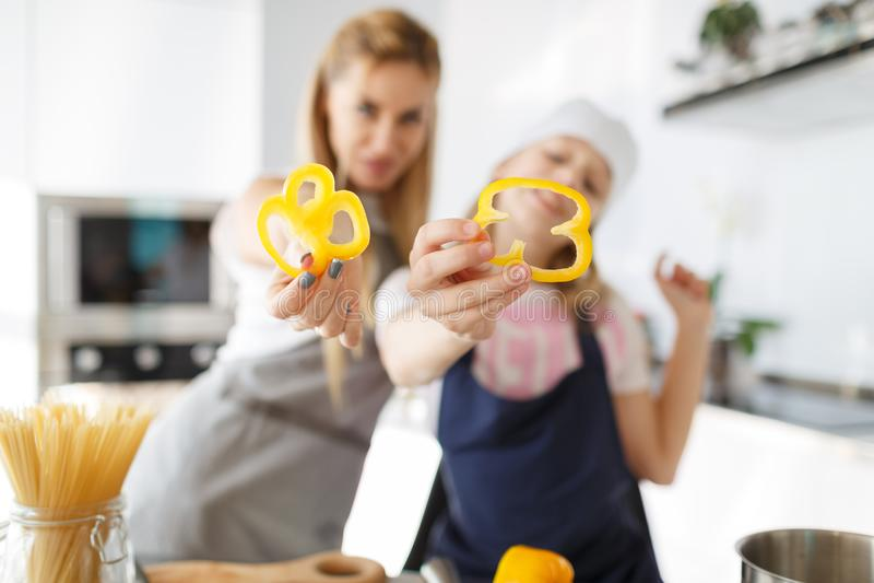 Ευτυχείς φέτες πιπεριών λαβής μητέρων και κορών στο δωμάτιο κουζινών Η διαδικασία ένα υγιές πιάτο από τα λαχανικά στοκ εικόνες