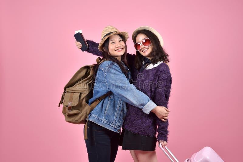Ευτυχείς φίλες τουριστών που συναντιούνται και που αγκαλιάζουν στον αερολιμένα, νέος ασιατικός ταξιδιώτης που έχει τη διασκέδαση  στοκ εικόνα