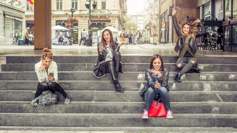 Ευτυχείς φίλοι κοριτσιών που κάθονται στα σκαλοπάτια πόλεων με το smartphone στοκ φωτογραφία με δικαίωμα ελεύθερης χρήσης