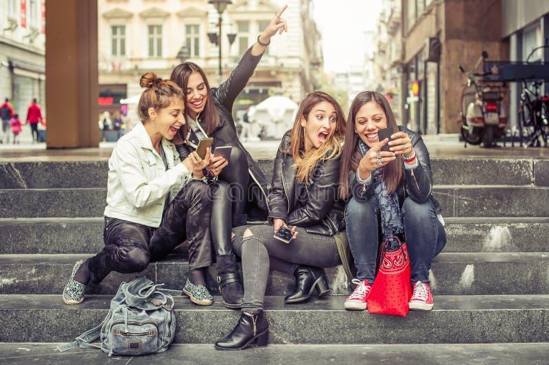 Ευτυχείς φίλοι κοριτσιών που κάθονται στα σκαλοπάτια πόλεων με το smartphone στοκ φωτογραφίες με δικαίωμα ελεύθερης χρήσης