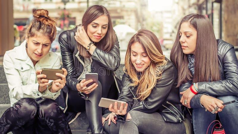 Ευτυχείς φίλοι κοριτσιών που κάθονται στα σκαλοπάτια πόλεων με το smartphone στοκ φωτογραφία