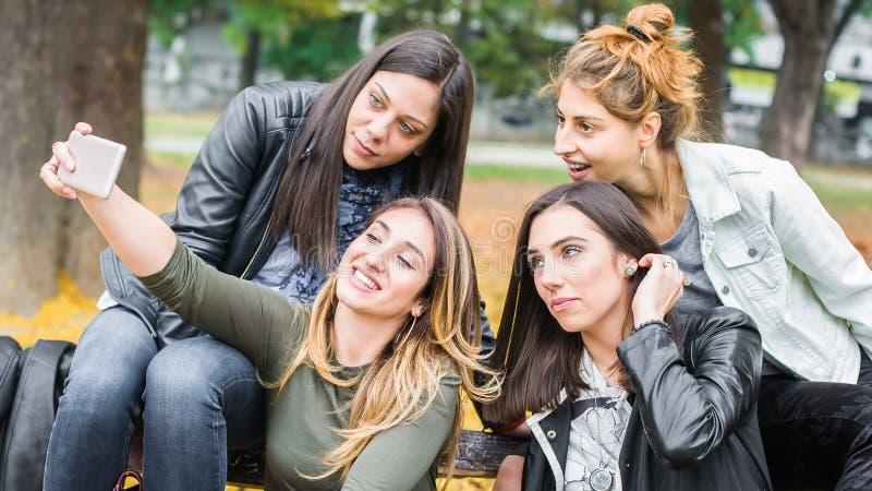 Ευτυχείς φίλοι κοριτσιών που κάθονται στον πάγκο πάρκων που παίρνει selflie τις φωτογραφίες στοκ εικόνα
