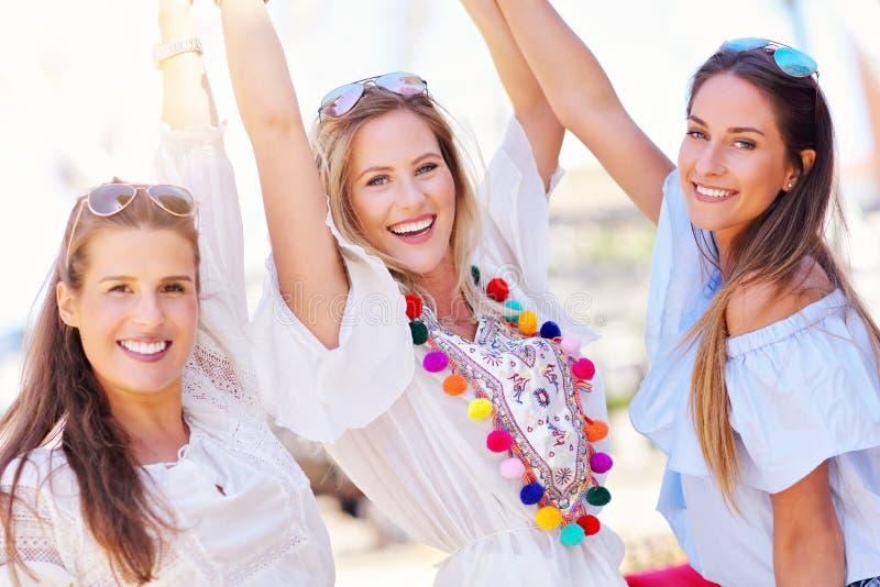 Ευτυχείς φίλοι κοριτσιών που κρεμούν έξω στην πόλη το καλοκαίρι στοκ εικόνες
