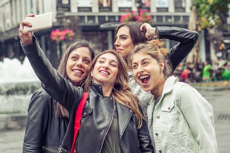 Ευτυχείς φίλοι κοριτσιών που παίρνουν selfie τις φωτογραφίες στην οδό στοκ φωτογραφία