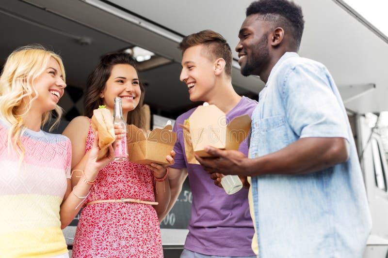 Ευτυχείς φίλοι με τα ποτά που τρώνε στο φορτηγό τροφίμων στοκ εικόνα με δικαίωμα ελεύθερης χρήσης