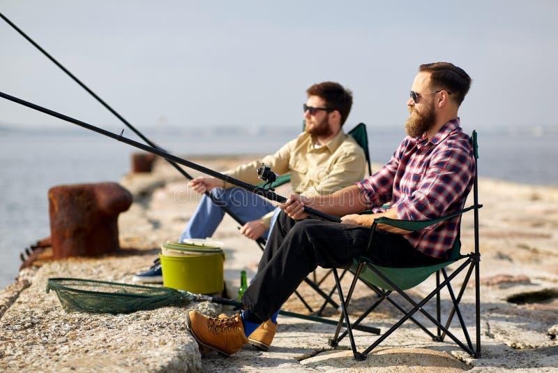Ευτυχείς φίλοι με την αλιεία των ράβδων στην αποβάθρα στοκ εικόνες με δικαίωμα ελεύθερης χρήσης