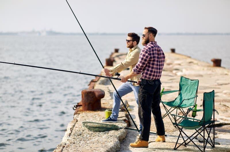 Ευτυχείς φίλοι με την αλιεία των ράβδων στην αποβάθρα στοκ φωτογραφία με δικαίωμα ελεύθερης χρήσης