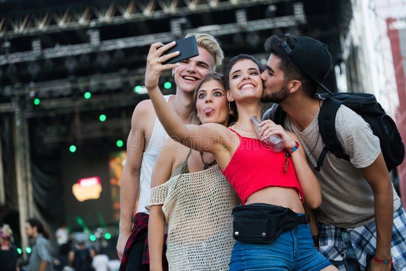 Ευτυχείς φίλοι που έχουν τη διασκέδαση στο φεστιβάλ μουσικής στοκ φωτογραφία με δικαίωμα ελεύθερης χρήσης