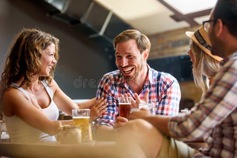 Ευτυχείς φίλοι που έχουν τη διασκέδαση στο φραγμό - καθιερώνοντες τη μόδα νέοι που πίνουν την μπύρα και που γελούν από κοινού στοκ φωτογραφία