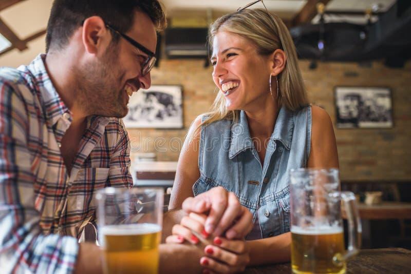 Ευτυχείς φίλοι που έχουν τη διασκέδαση στο φραγμό - νέα καθιερώνουσα τη μόδα μπύρα κατανάλωσης ζευγών και γέλιο από κοινού στοκ φωτογραφία