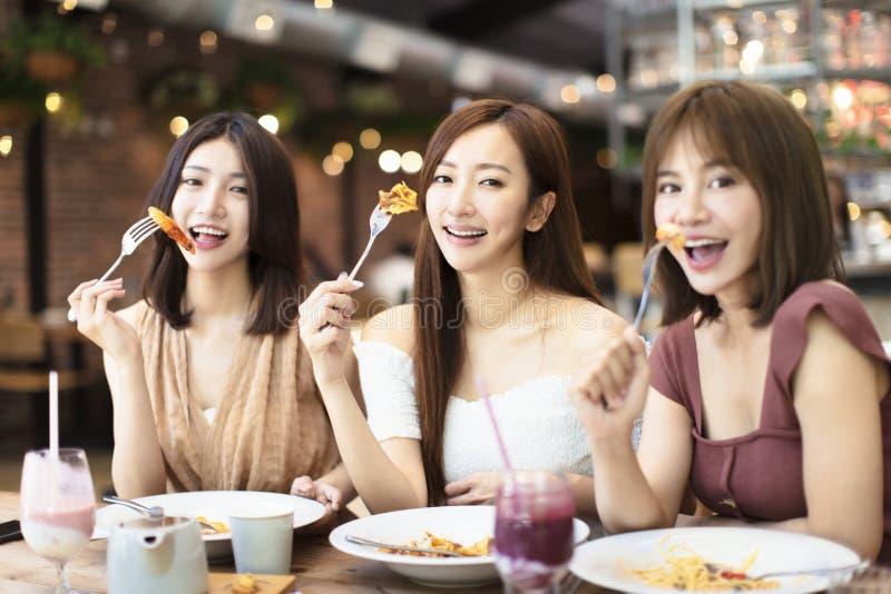 Ευτυχείς φίλοι που έχουν το γεύμα στο εστιατόριο στοκ φωτογραφία