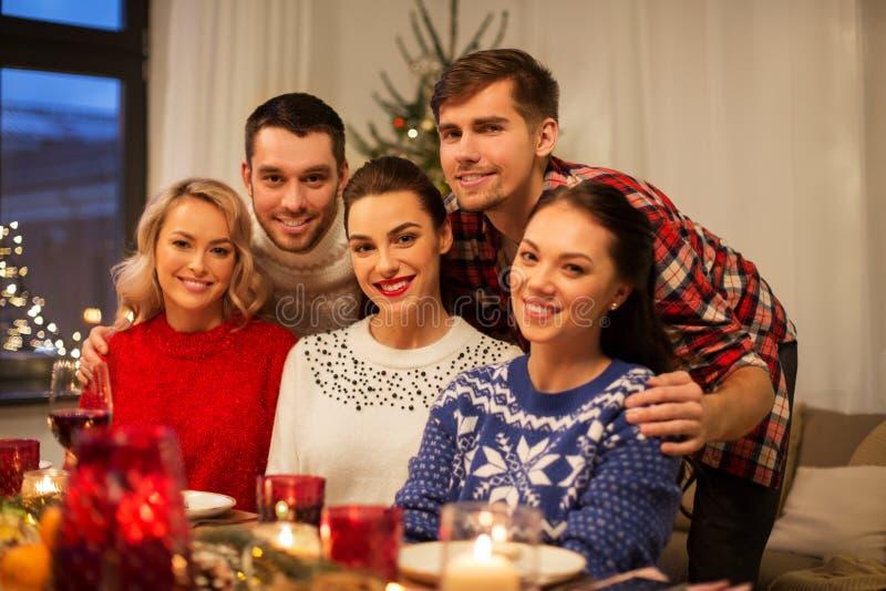 Ευτυχείς φίλοι που γιορτάζουν τα Χριστούγεννα στο σπίτι στοκ εικόνες
