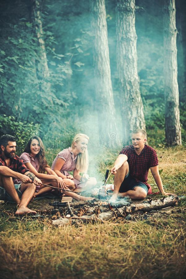 Ευτυχείς φίλοι που κάθονται την πυρά προσκόπων στην έννοια βραδιού, φιλίας και ελεύθερου χρόνου Νέα χαμογελώντας ζεύγη που έχουν στοκ φωτογραφία με δικαίωμα ελεύθερης χρήσης
