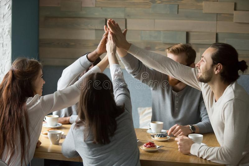 Ευτυχείς φίλοι που συναντιούνται στον καφέ που δίνει υψηλά πέντε για τη φιλία στοκ εικόνες