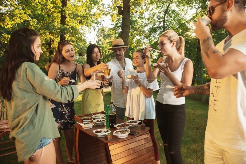 Ευτυχείς φίλοι που τρώνε και που πίνουν τις μπύρες στο γεύμα σχαρών στο χρόνο ηλιοβασιλέματος στοκ φωτογραφία