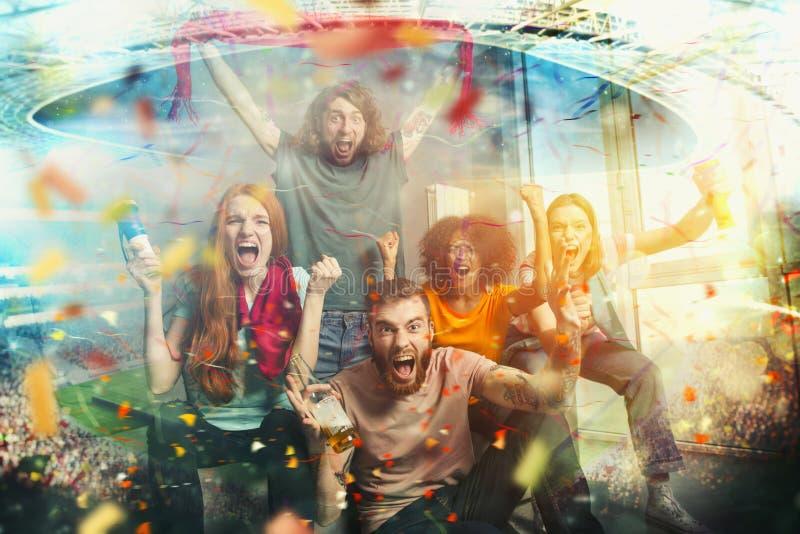 Ευτυχείς φίλοι των οπαδών ποδοσφαίρου που προσέχουν το ποδόσφαιρο στη TV και που γιορτάζουν τη νίκη στοκ φωτογραφία με δικαίωμα ελεύθερης χρήσης