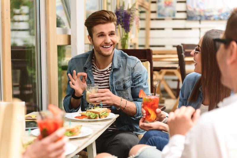 Ευτυχείς φίλοι που έχουν το μεσημεριανό γεύμα στον καφέ στοκ φωτογραφία με δικαίωμα ελεύθερης χρήσης