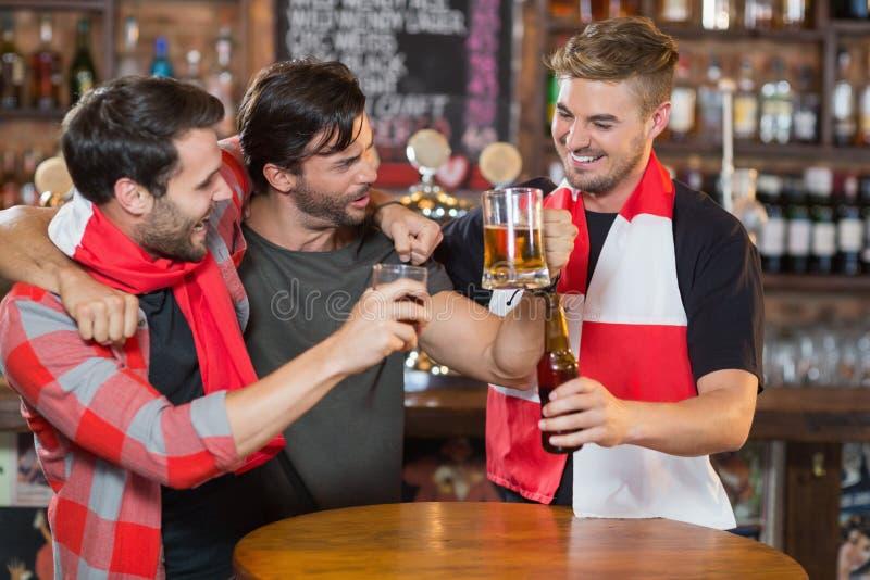 Ευτυχείς φίλοι που απολαμβάνουν στο μπαρ στοκ φωτογραφίες