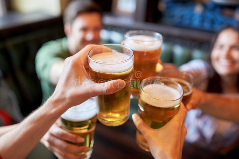 Ευτυχείς φίλοι που πίνουν την μπύρα στο φραγμό ή το μπαρ στοκ εικόνες
