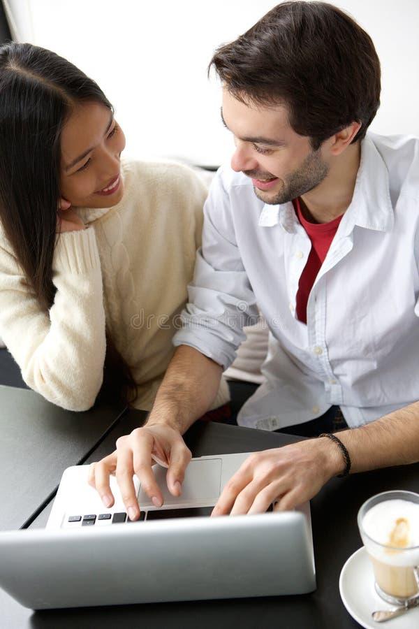 Ευτυχείς φίλοι που χαμογελούν και που χρησιμοποιούν το lap-top στοκ φωτογραφία με δικαίωμα ελεύθερης χρήσης