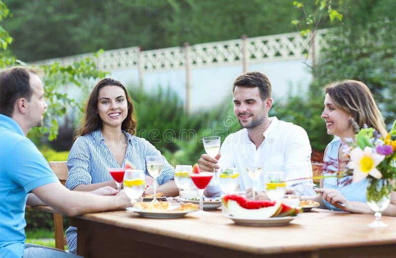 Ευτυχείς φίλοι που ψήνουν τα γυαλιά κρασιού στον κήπο ενώ έχοντας το λ στοκ φωτογραφίες
