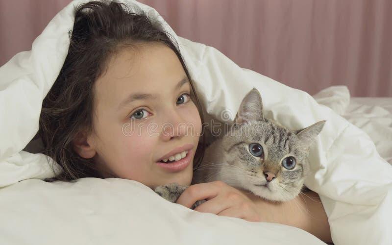 Ευτυχείς φιλιά και συζητήσεις κοριτσιών εφήβων με την ταϊλανδική γάτα στο κρεβάτι στοκ φωτογραφία με δικαίωμα ελεύθερης χρήσης