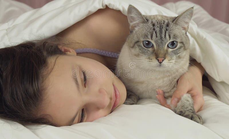 Ευτυχείς φιλιά και συζητήσεις κοριτσιών εφήβων με την ταϊλανδική γάτα στο κρεβάτι στοκ φωτογραφία