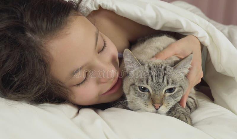 Ευτυχείς φιλιά και συζητήσεις κοριτσιών εφήβων με την ταϊλανδική γάτα στο κρεβάτι στοκ εικόνα με δικαίωμα ελεύθερης χρήσης