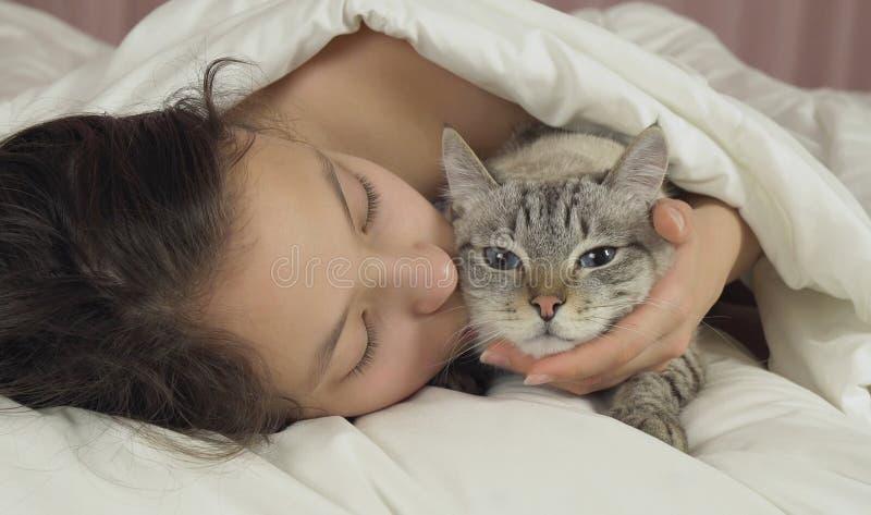 Ευτυχείς φιλιά και συζητήσεις κοριτσιών εφήβων με την ταϊλανδική γάτα στο κρεβάτι στοκ φωτογραφίες