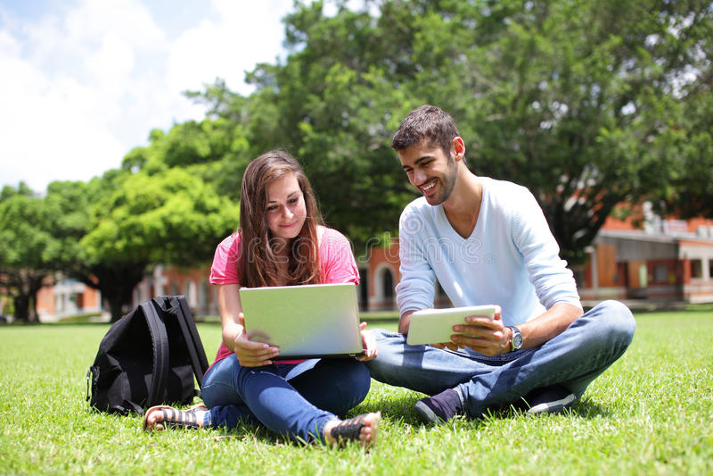 Ευτυχείς φοιτητές πανεπιστημίου που χρησιμοποιούν τον υπολογιστή στοκ εικόνα