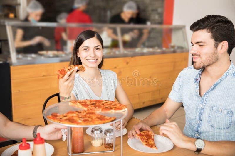 Ευτυχείς χαμογελώντας άνδρες και νέες γυναίκες που μοιράζονται την πίτσα στοκ φωτογραφία