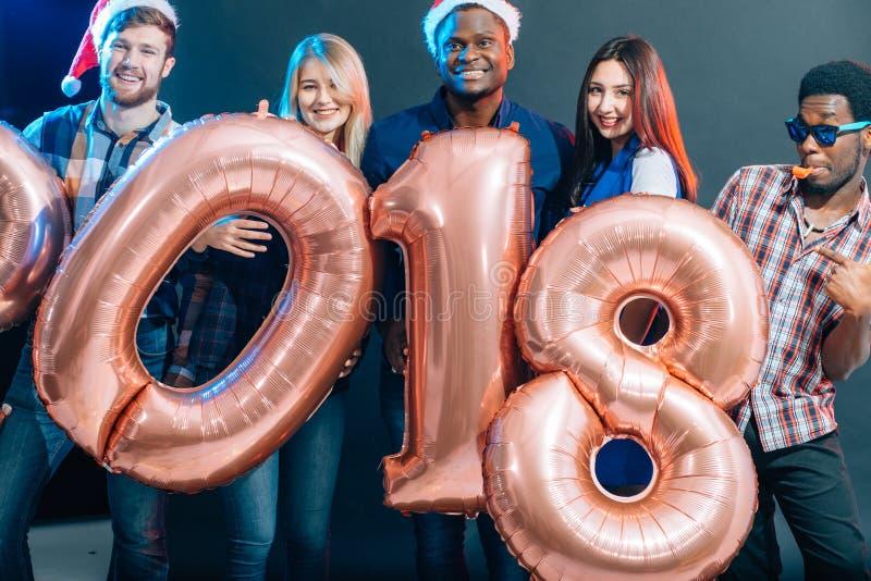 Ευτυχείς χαμογελώντας άνθρωποι που κρατούν τα χρυσά μπαλόνια αριθμού, σύμβολο έτους του 2018 στοκ φωτογραφίες