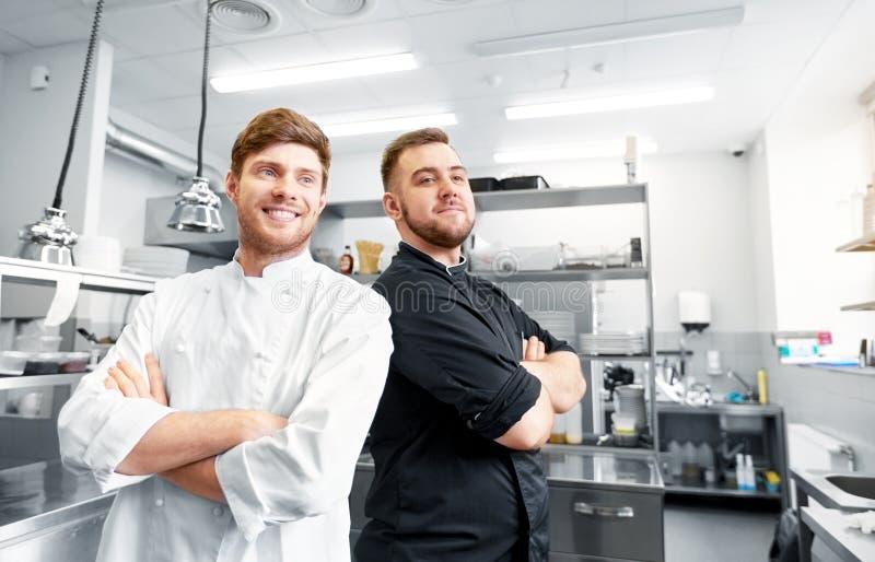 Ευτυχείς χαμογελώντας αρχιμάγειρας και μάγειρας στην κουζίνα εστιατορίων στοκ εικόνα με δικαίωμα ελεύθερης χρήσης