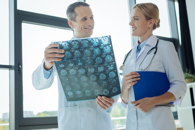 Ευτυχείς χαρούμενοι γιατροί που εξετάζουν ο ένας τον άλλον στοκ εικόνες
