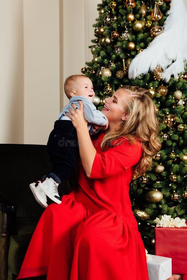 Ευτυχείς όμορφες νέες μητέρα και αυτή λίγη 1χρονη συνεδρίαση μωρών στην πολυθρόνα στοκ εικόνες