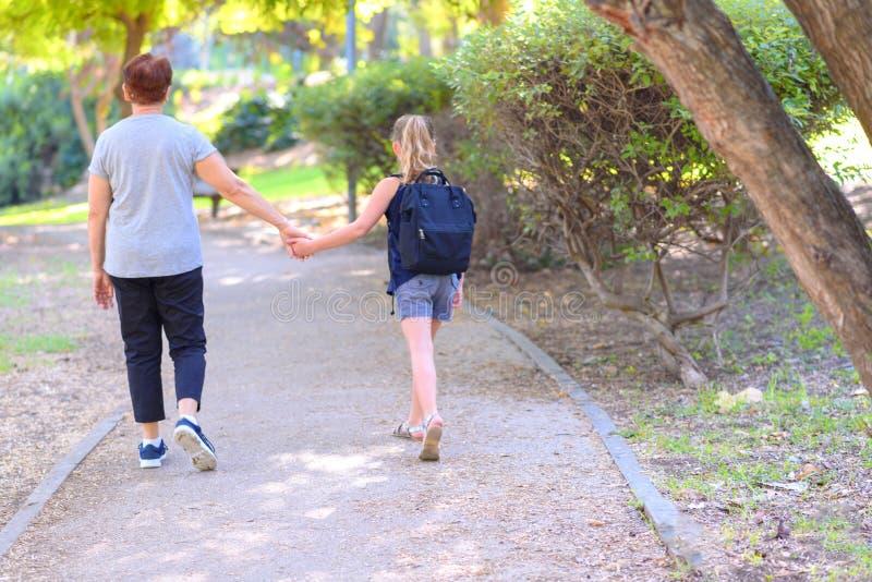 Ευτυχείς Grandma και εγγονή που περπατούν στο σχολείο στην οδό στο πάρκο φθινοπώρου στοκ εικόνα