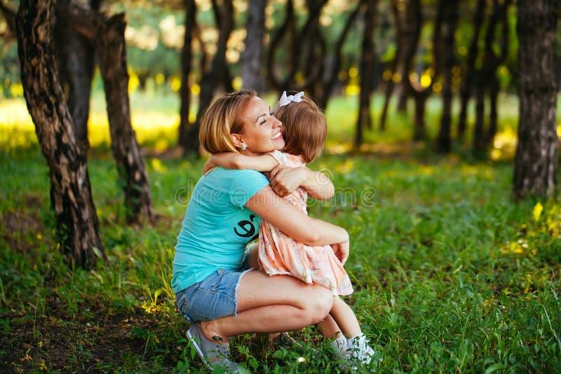 Ευτυχείς mom και κόρη που χαμογελούν στη φύση στοκ φωτογραφίες